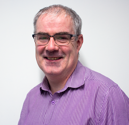 A front profile of John Keane, turned slightly to the left, he is wearing a purple buttoned shirt and rectangular glassess